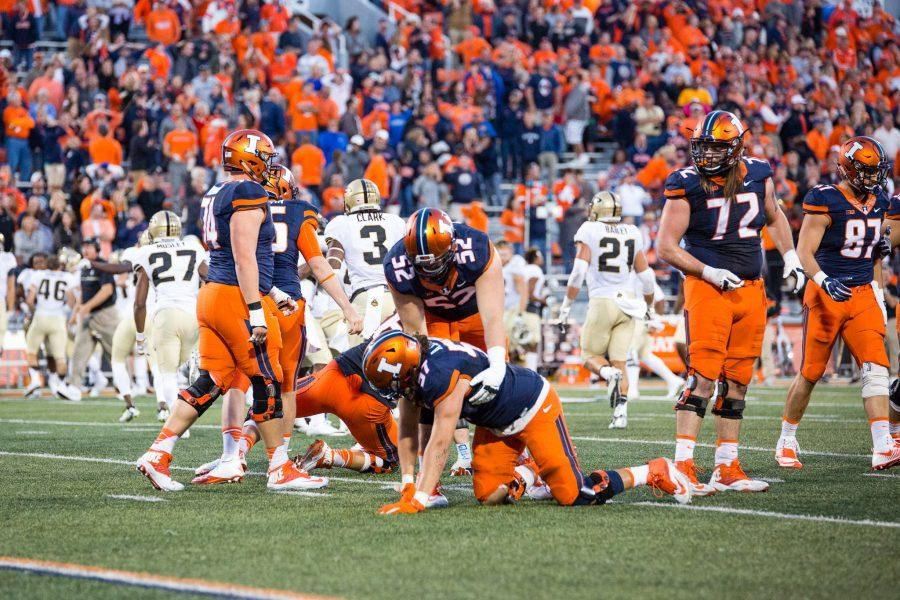 Illinois offensive lineman Austin Schmidt (57) gets helped up by Adam Solomon (52) after place kicker Chase McLaughlin missed the field goal to win the game at the end of the fourth quarter in the game against Purdue at Memorial Stadium on October 8. The Illini lost 34-31.