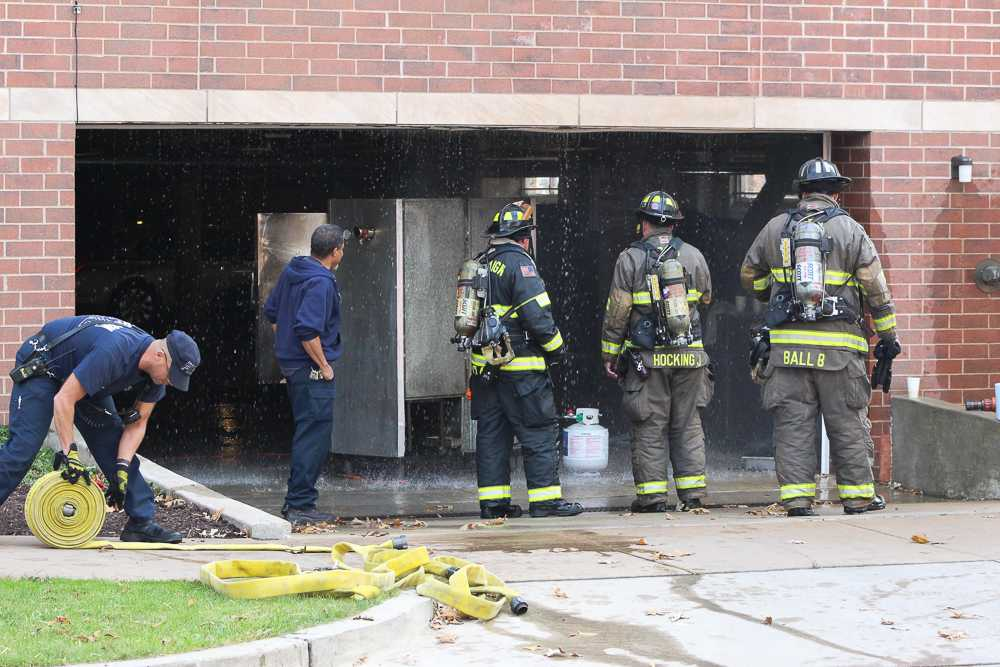 Champaign firefighters look over the situation at Presby Hall's parking garage after a cooking fire started Friday.