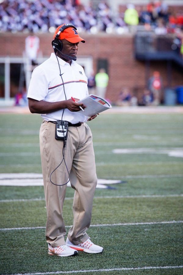 Illinois head coach Lovie Smith looks at the playbook during a TV timeout in the game against Purdue at Memorial Stadium on Saturday, October 8. The Illini lost 34-31.