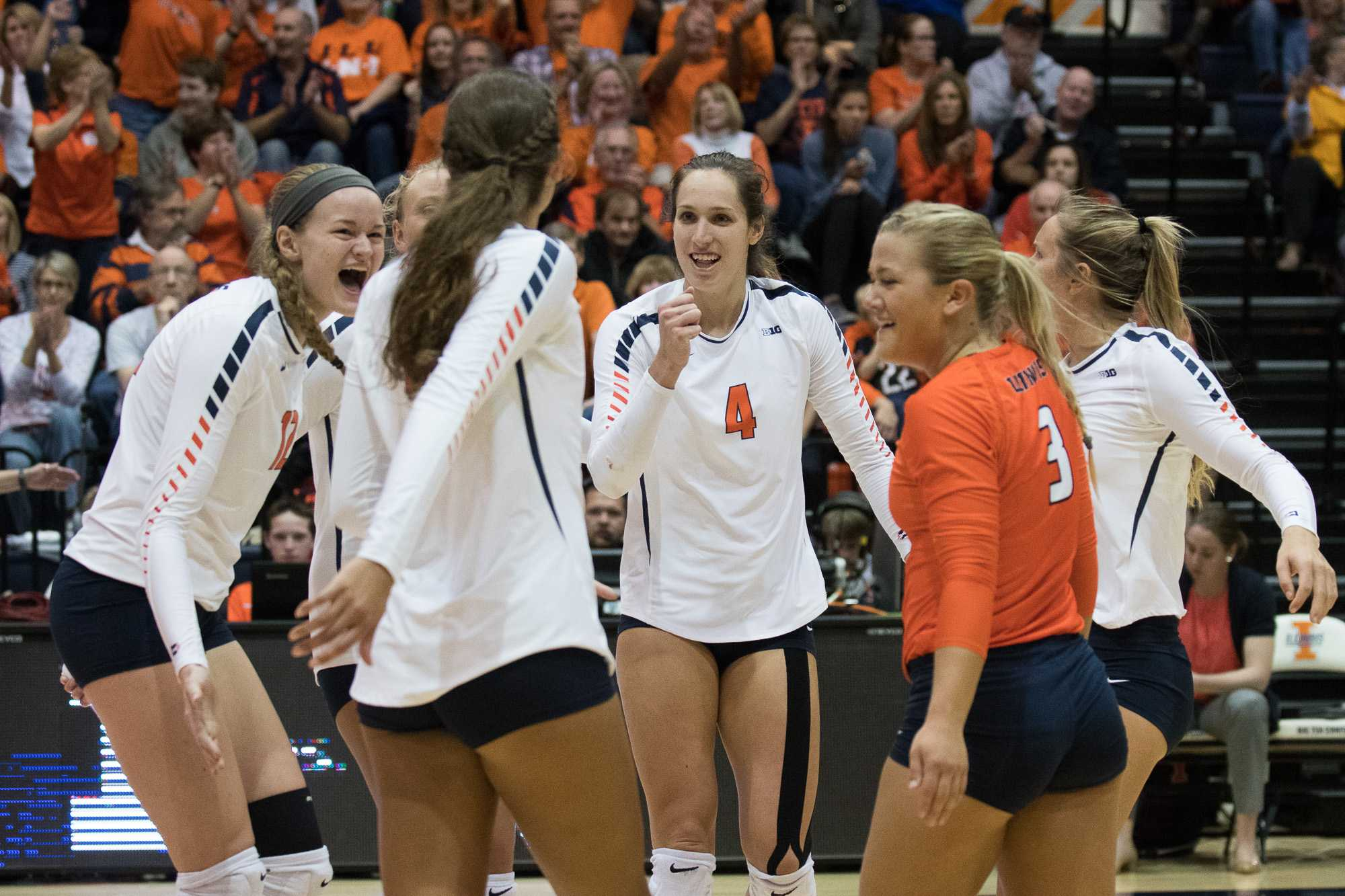 Players (Michelle Strizak (4)) on the Women's Volleyball team cheer and congratulate each other after scoring a point.
