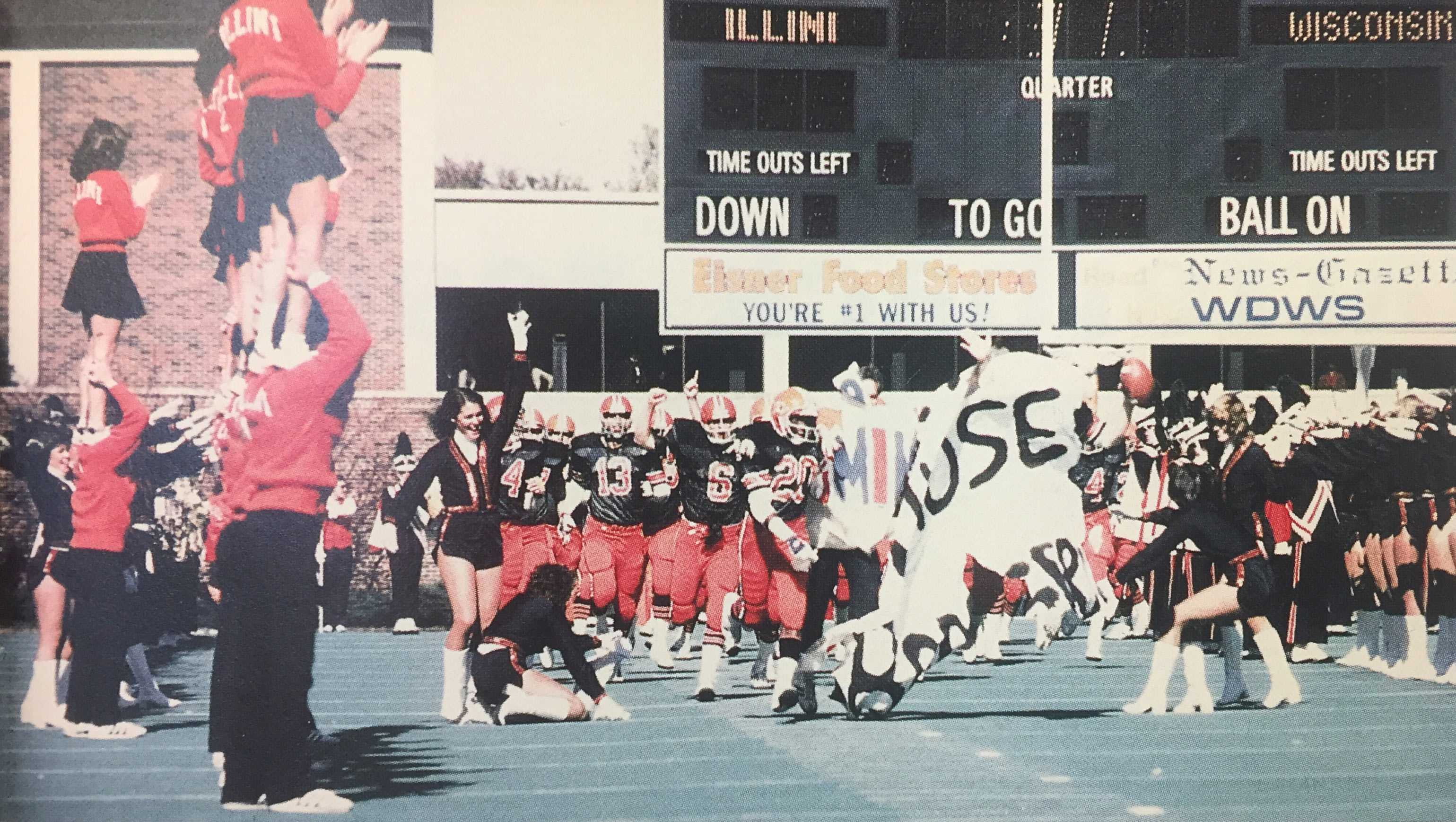 The Illini break through a banner at the 1981 Homecoming football game while the cheerleading squad encourages the football team from the side.