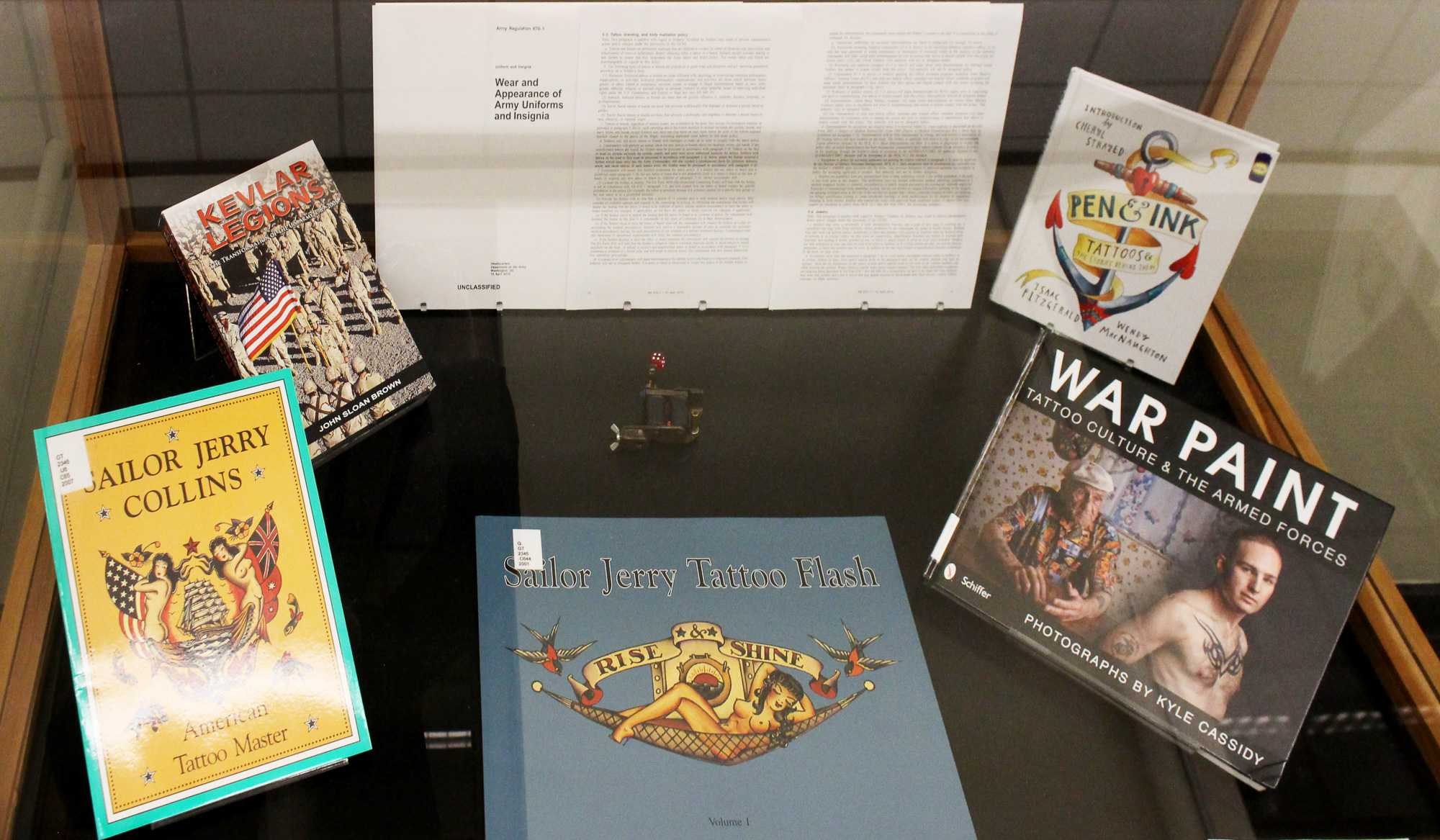 Artifacts for the Symbols of Service exhibit sit in one of six display cases on the first floor of the Main Library. The gallery focuses on U.S. veterans and their tattoos, while also addressing other topics such as readjusting to civilian life after military service.