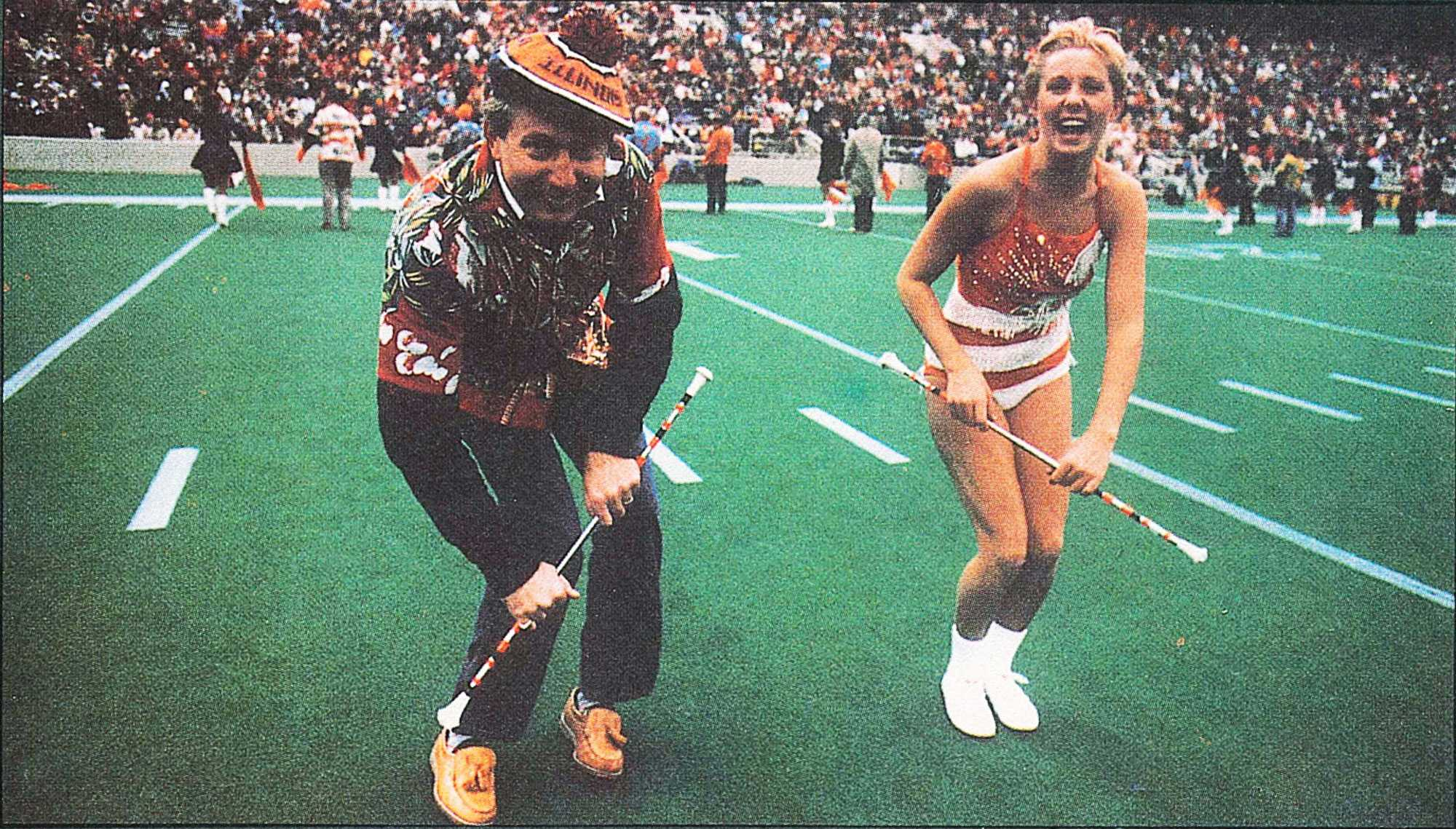 Molly Nicholas, alumni, and her dad show the crowd where she got her talent at the Dad's Weekend football game in 1986.