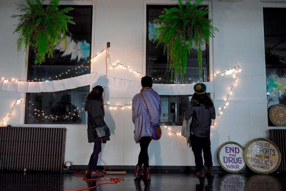 Students read the pieces from the poem wall at the Yikes!!!: A Showcase on Survival at the Independent Media Center in Urbana on Friday, November 11.