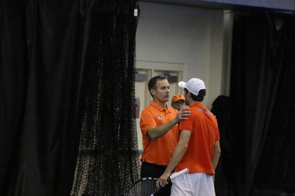 Head coach Brad Dancer talks to Illinois' Aleks Vukic in the match against TCU at the Atkins Tennis Center on Feb. 28.