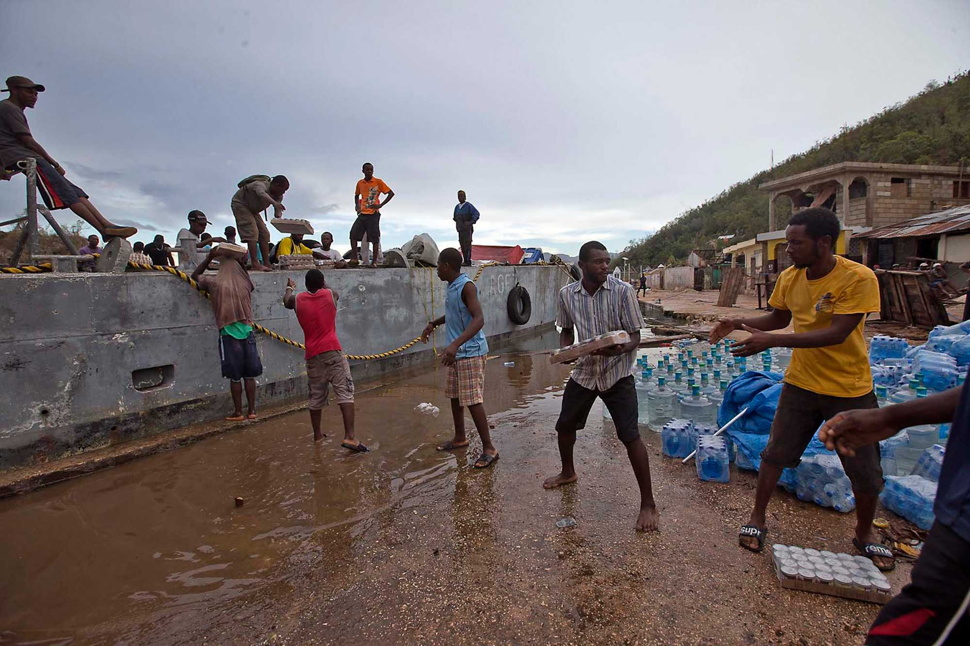 Men unload food from Food for the Poor off a barge to the coastal town of Pestel, Haiti, on Thursday, Oct. 13, 2016. Pestel was damaged severely by the passing of Hurricane Matthew. (Patrick Farrell/Miami Herald/TNS)