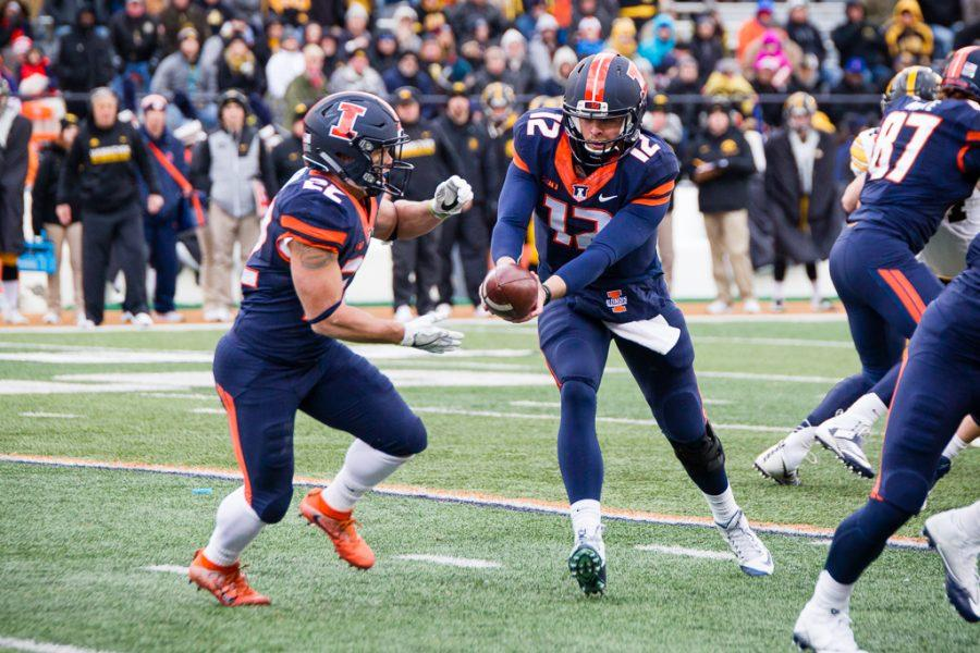 Illinois quarterback Wes Lunt (12) hands the ball off to running back Kendrick Foster (22) during the first half of the game against Iowa at Memorial Stadium on Saturday. The Illini are losing 7-0 at halftime.