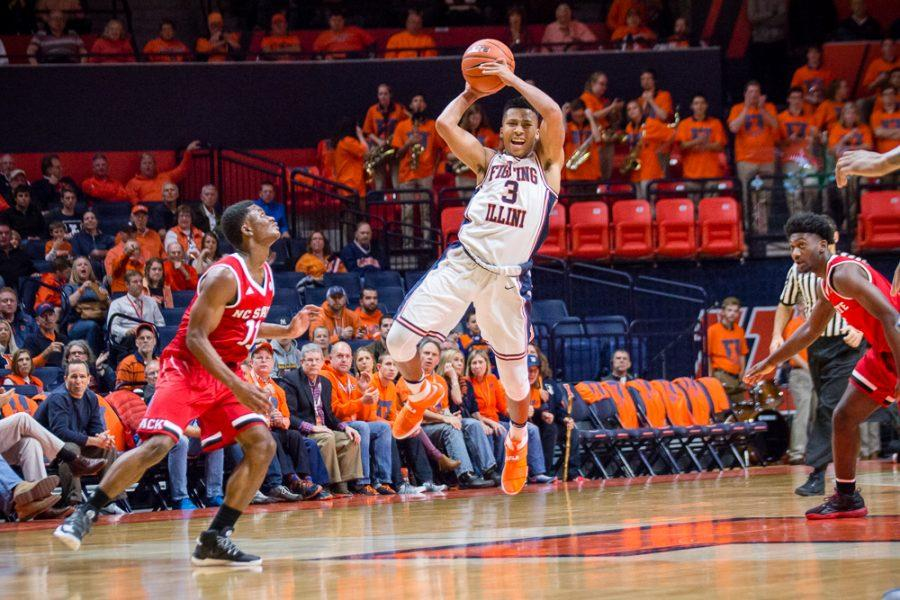 Illinois' Te'Jon Lucas (3) jumps up to pass the ball off a fast break during the game against North Carolina State at State Farm Center on Tuesday, November 29. The Illini won 88-74.