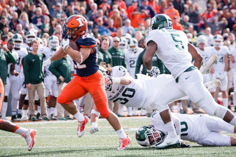 Illinois running back Kendrick Foster (22) runs through a pair of Michigan State defenders for a touchdown during the first half of game against Michigan State at Memorial Stadium on Saturday, November 5. The Illini lead 7-6 at halftime.