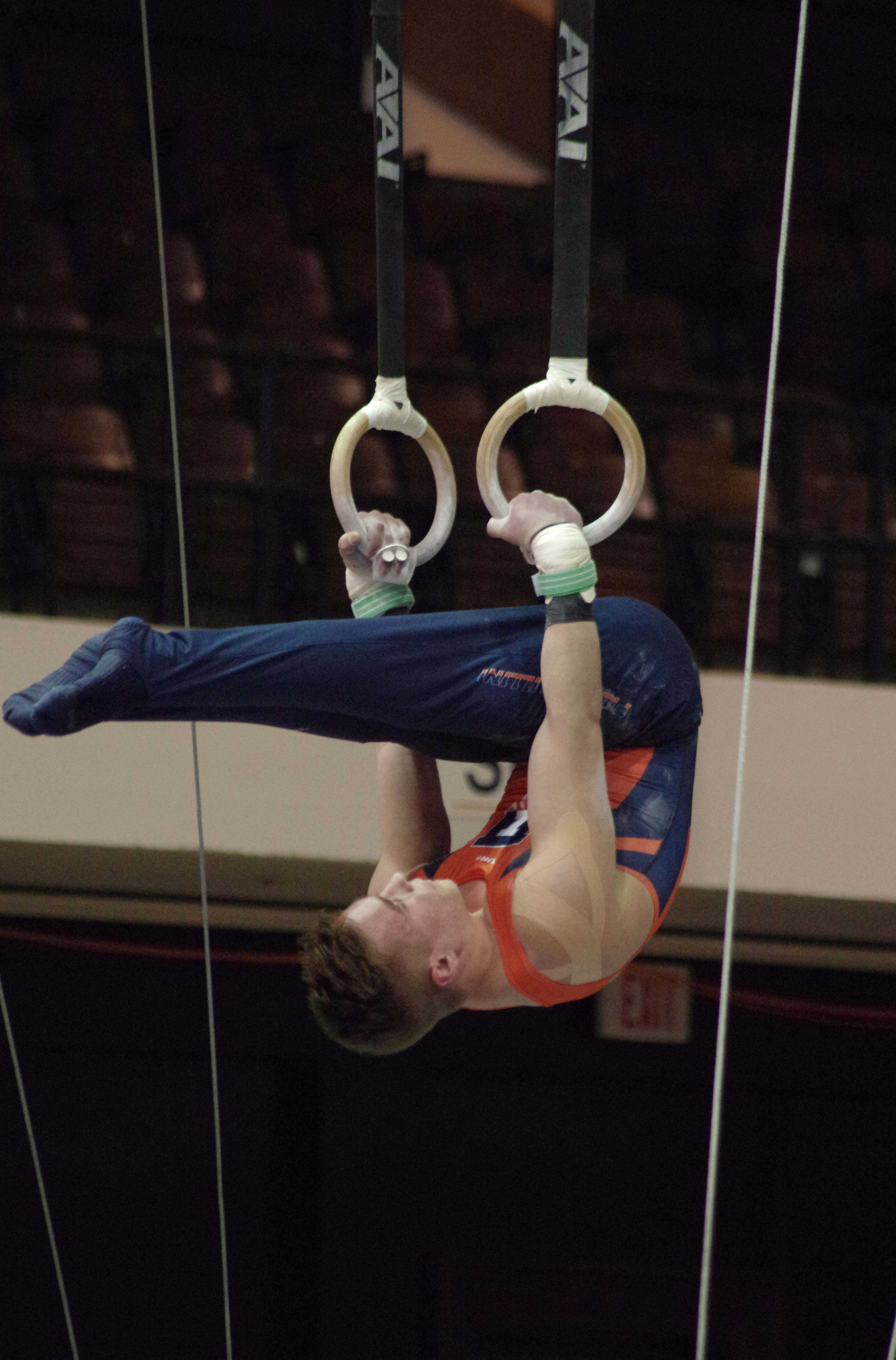 Illinois' Dennis Minton performs his routine on the rings at the meet against Michigan on March 12, 2016.