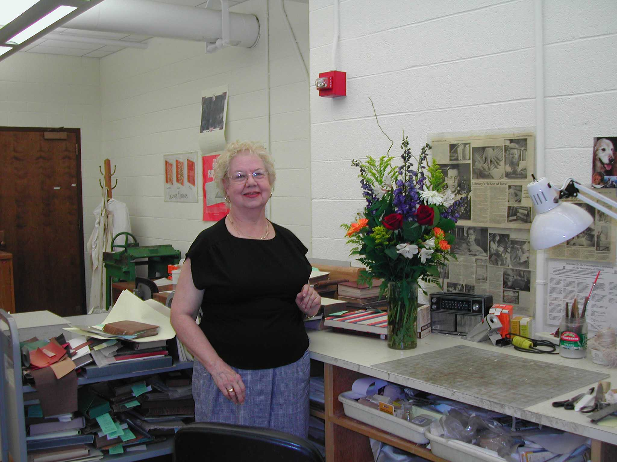 Jane Gammon stands at her conservation bench at the old conservation lab in the Main Library. 2004.