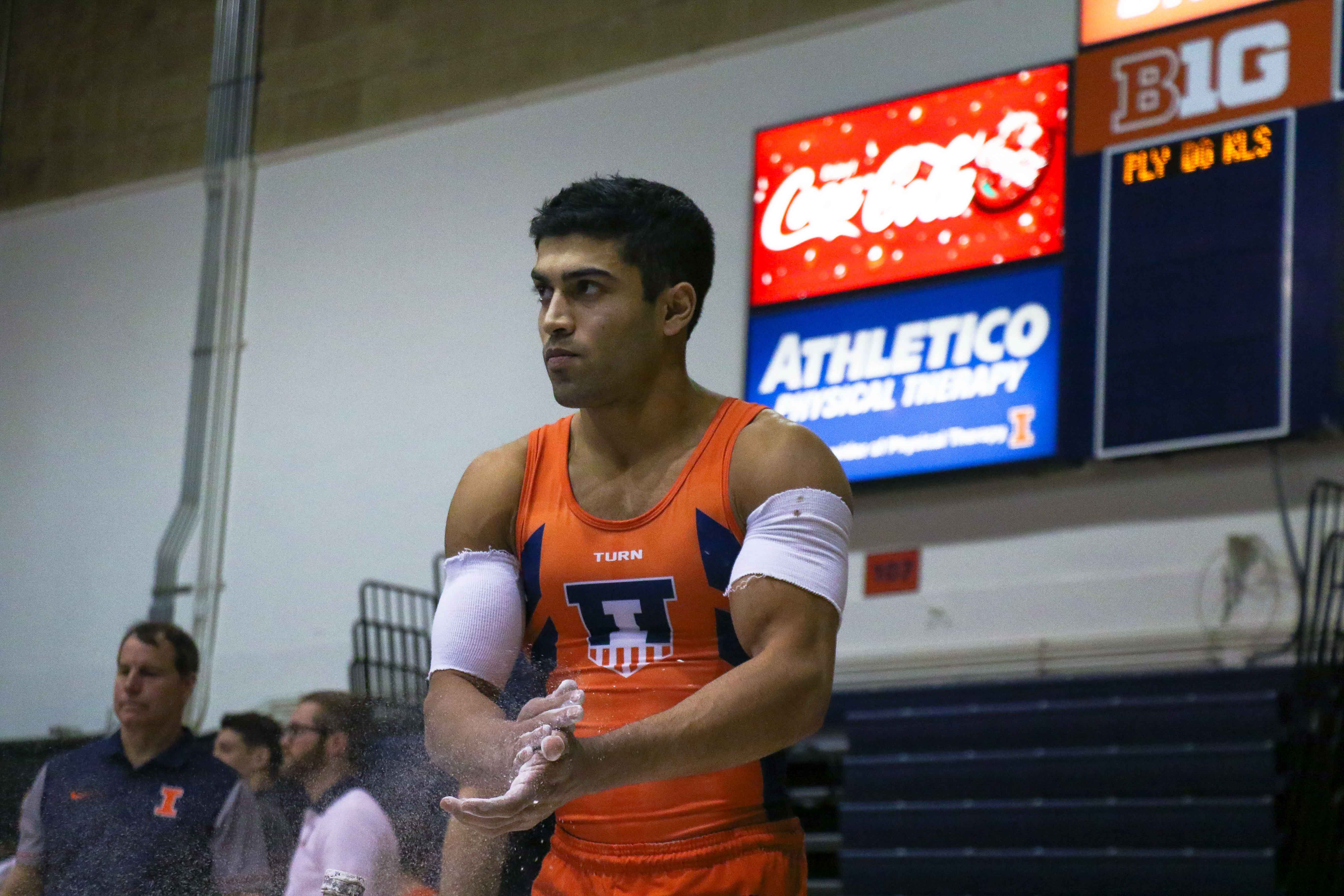 Illinois' Joey Peters prepares for the parallel bars in the meet against Minnesota at Huff Hall on Saturday, Jan. 28.