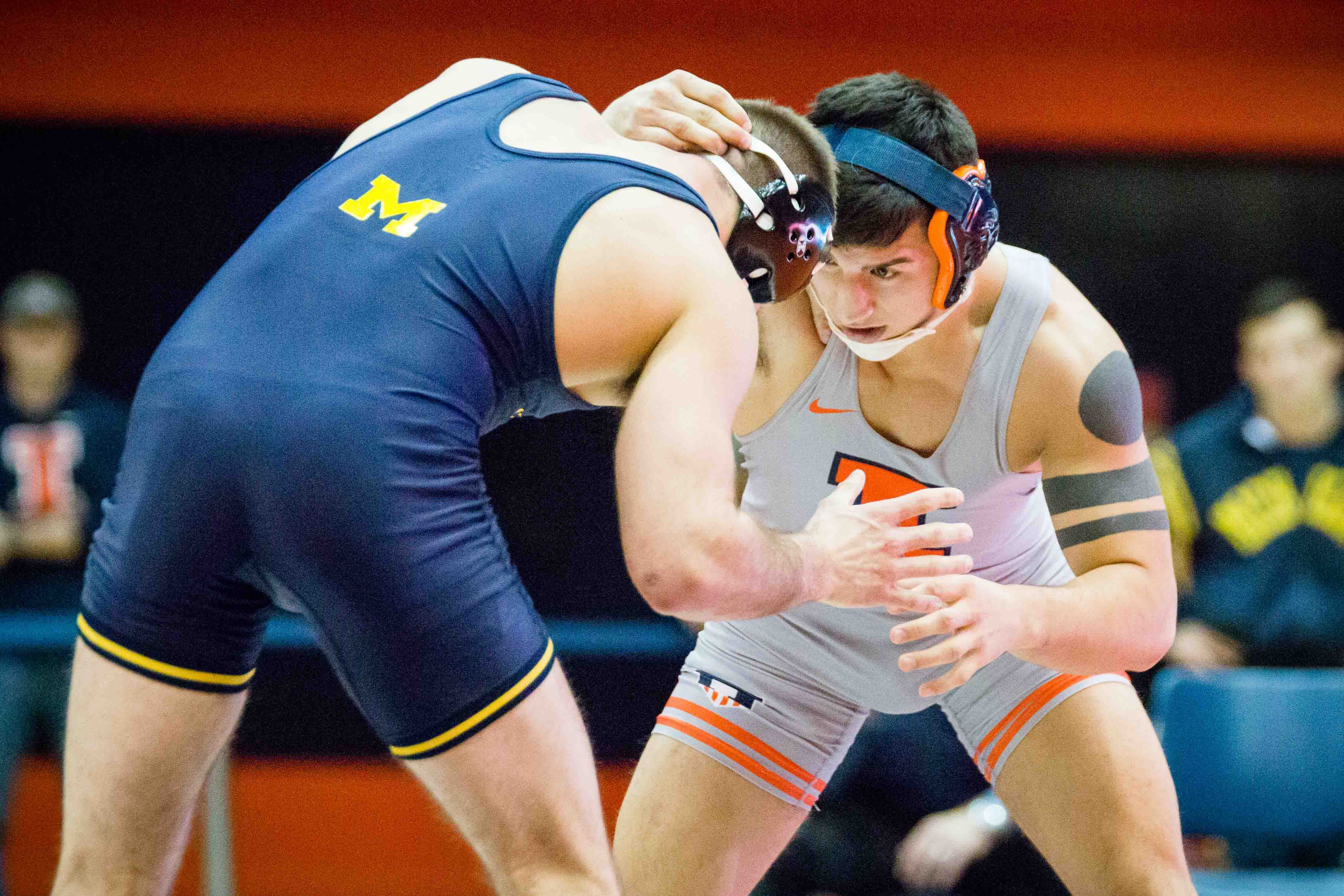 Illinois' Isaiah Martinez wrestles with Michigan's Logan Massa in the 165 pound weight class during the match at Huff Hall on Friday, January 20. Martinez won by decision and the Illini defeated the Wolverines 34-6.