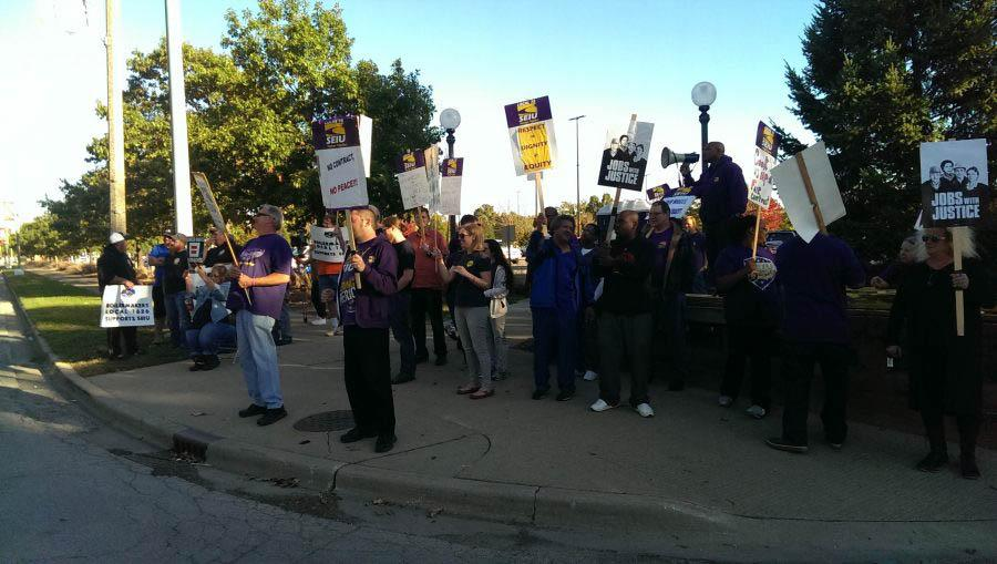 Aaron Ammons, right, with megaphone, leads members of the Service Employees International Union Local 73 in October. While the union contract negotiations have been going on for months, this is the first picket of 2017.