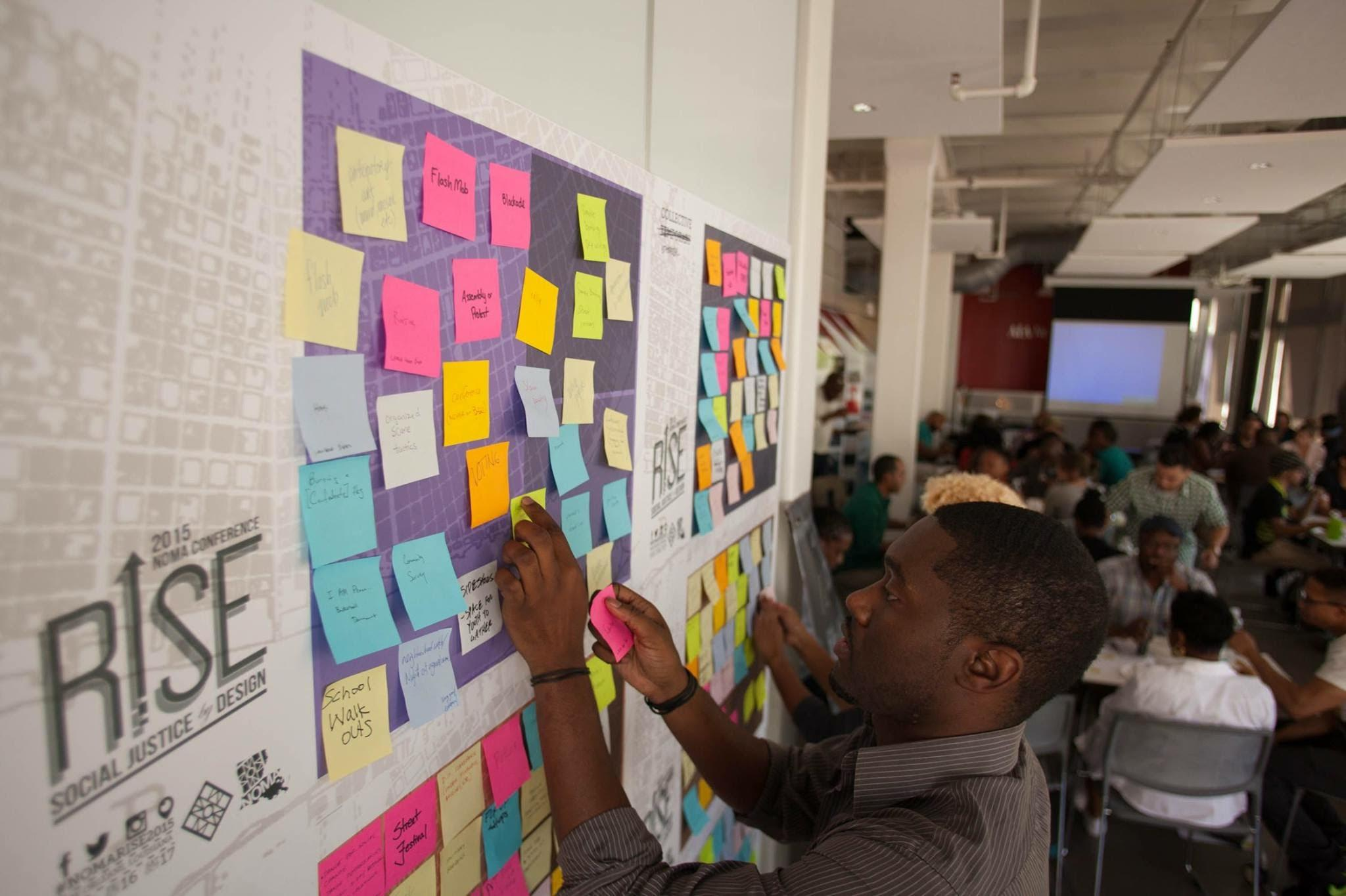 Bryan C Lee Jr. puts up post-it notes at a Design as Protest workshop in New Orleans. Design as Protest brings together artists, architects, and designers to address social injustices.