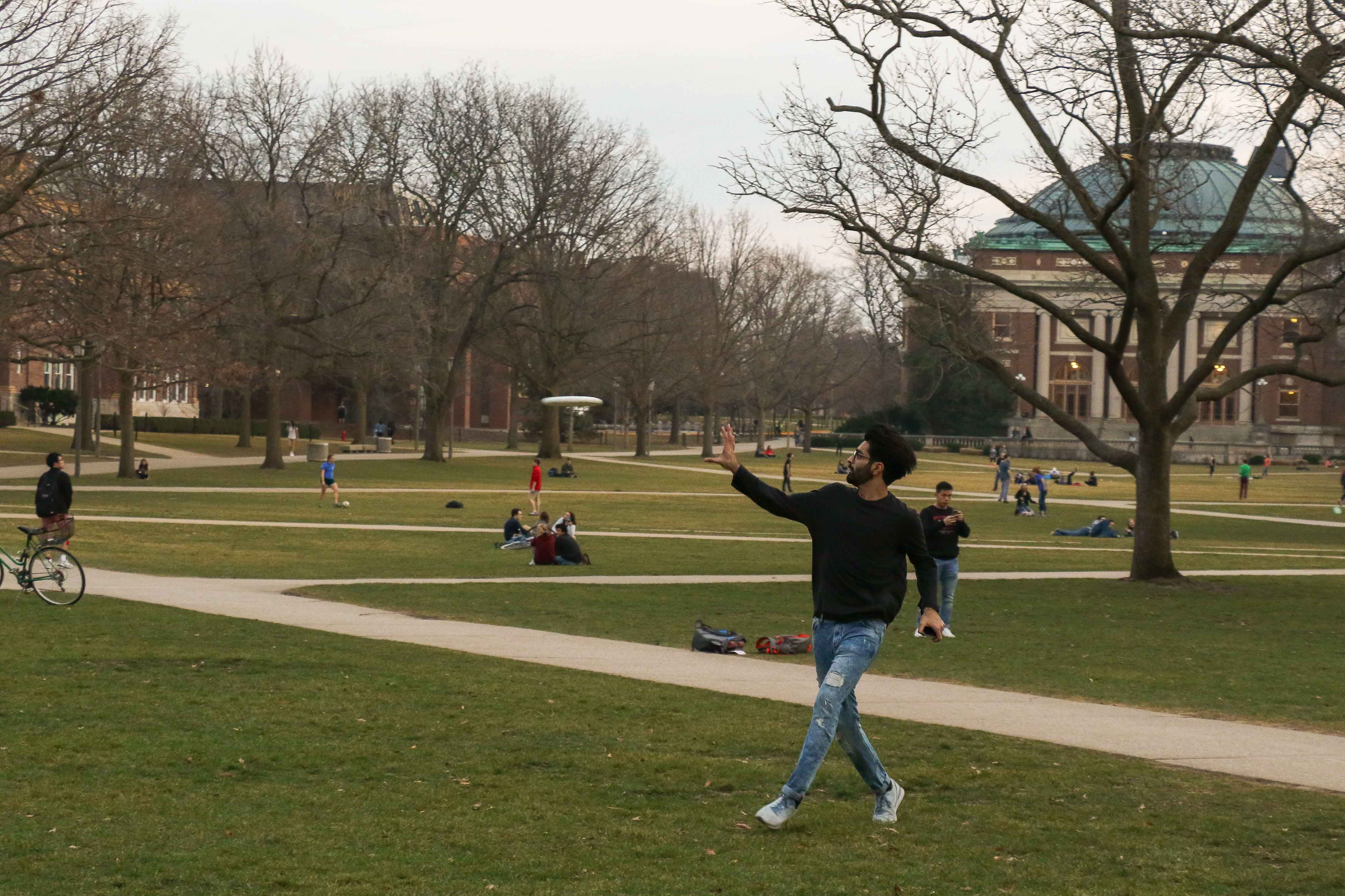 Students take advantage of the warm weather and play frisbee on the Main Quad.