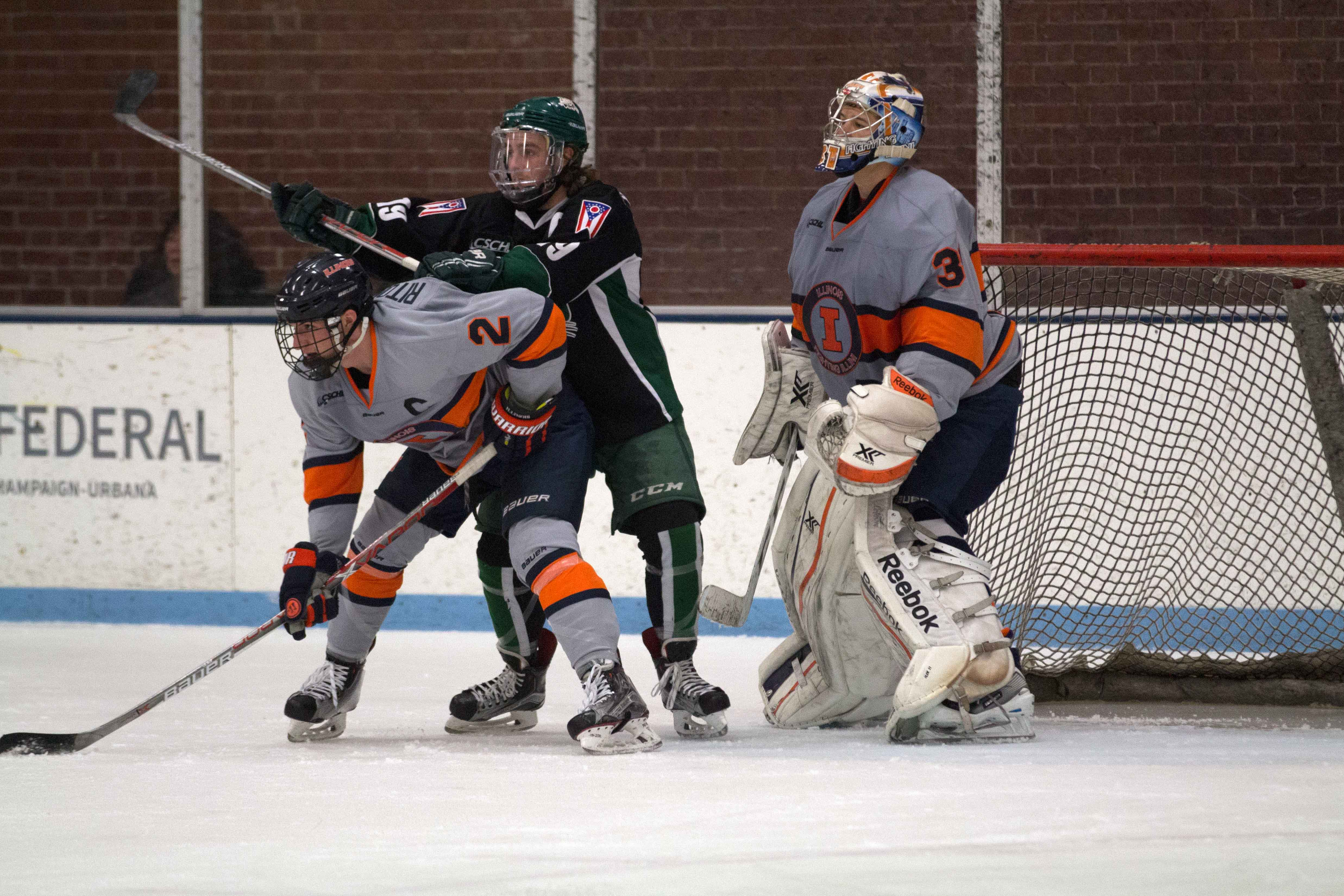Joey Ritondale (2) fights off Ohio's forward at the Ice Arena on Saturday. The Illini fell to Ohio, 4-1.