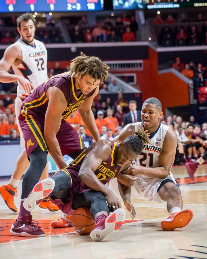 Illinois' Malcolm Hill (21) fights for the ball with Minnesota's Akeem Springs (0) during the game against Minnesota at State Farm Center on Saturday, February 4. The Illini lost 68-59.
