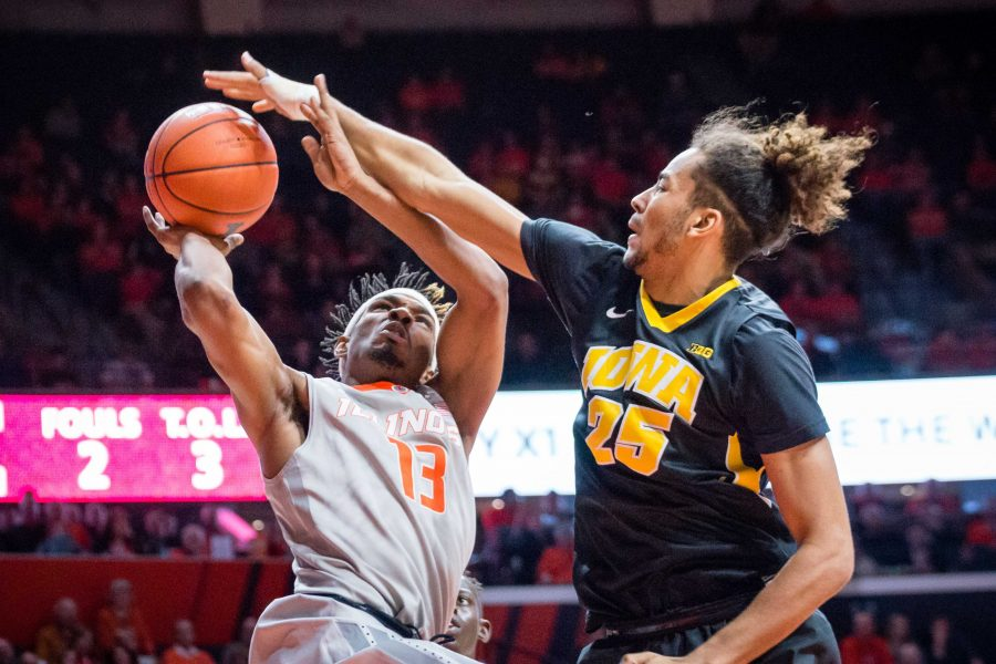 Illinois' Tracy Abrams (13) gets blocked by Iowa's Dom Uhl (25) during the game against Iowa at State Farm Center on Wednesday, January 25. The Illini won 76-64.