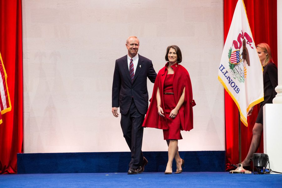 Governor-elect Bruce Rauner steps onto the stage to be sworn into office at the Prairie Capital Convention Center on Monday, Jan. 12, 2015 in Springfield, Ill. His wife Diane holds the Bible and Honorable Sharon Johnson Coleman administers the oath.