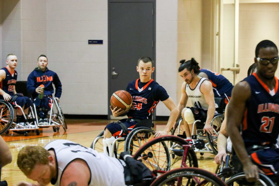 Spencer Heslop carries the ball as the Illini Men's Wheelchair Basketball team plays against the Canadian Academy.