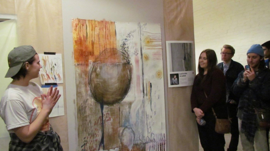 Visitors watch an artist explain their work at last year's 8 to Create event. 8 to Create will host their third-annual showing from 10 a.m. to 6 p.m. Saturday at [co][lab] in downtown Urbana.