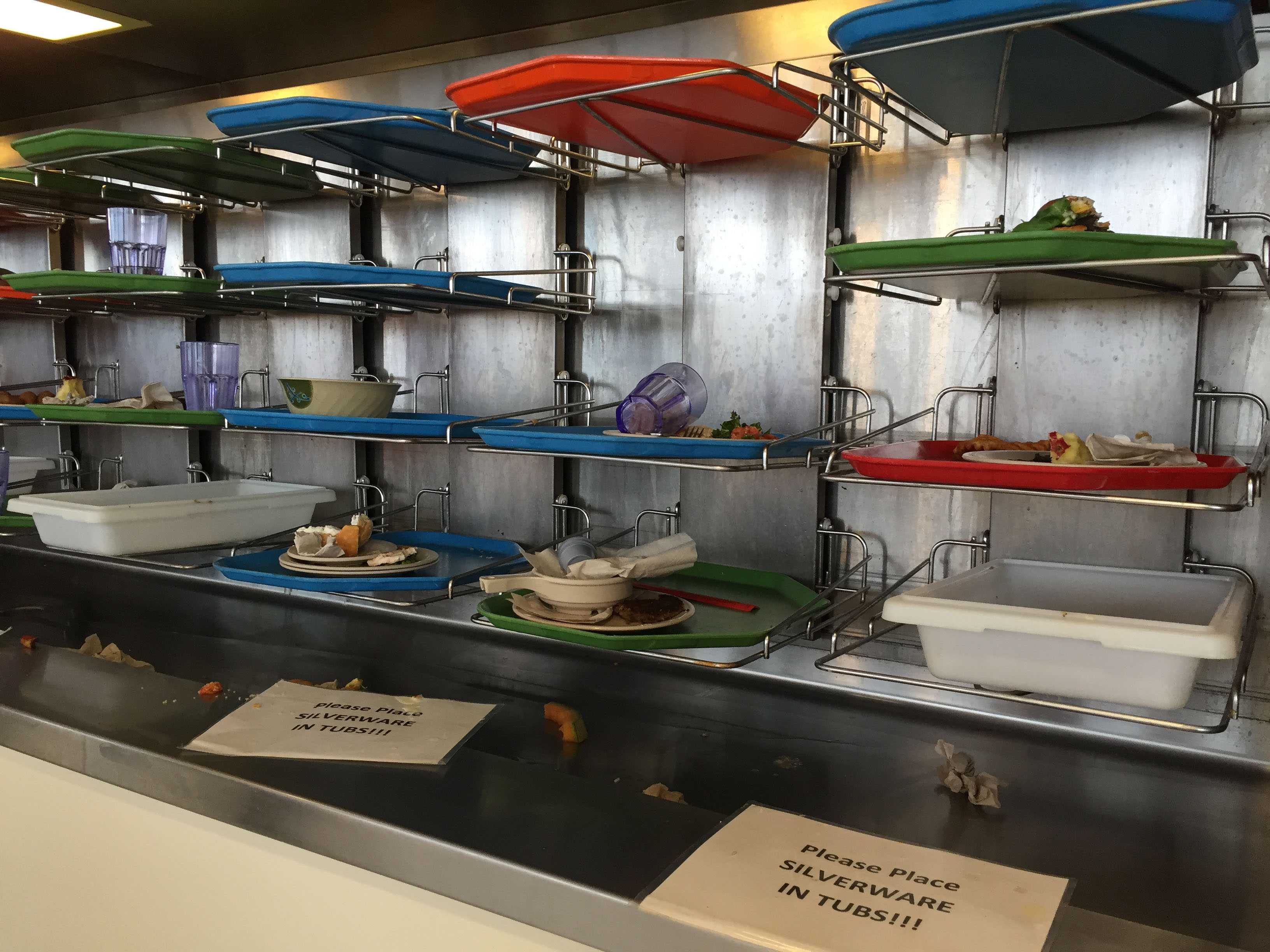 Students put their food waste, along with their plates and utensils, on a moving tray conveyor belt in the Ikenberry Dinning Hall.