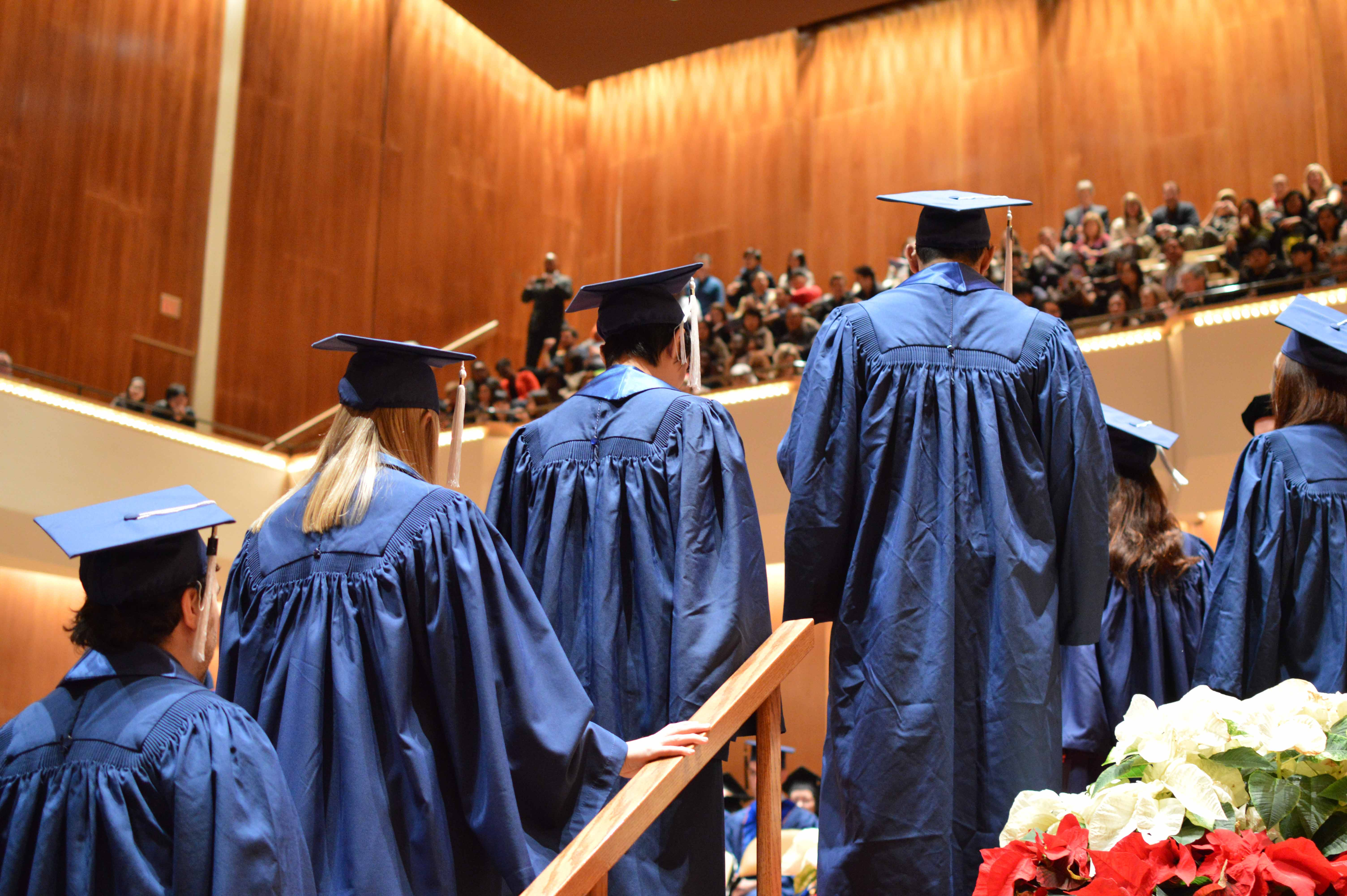 Graduating students from the College of Liberal Arts and Sciences walk onto stage during the fall convocation ceremony. A petition is circulating among students to bring former President Barack Obama to Convocation.