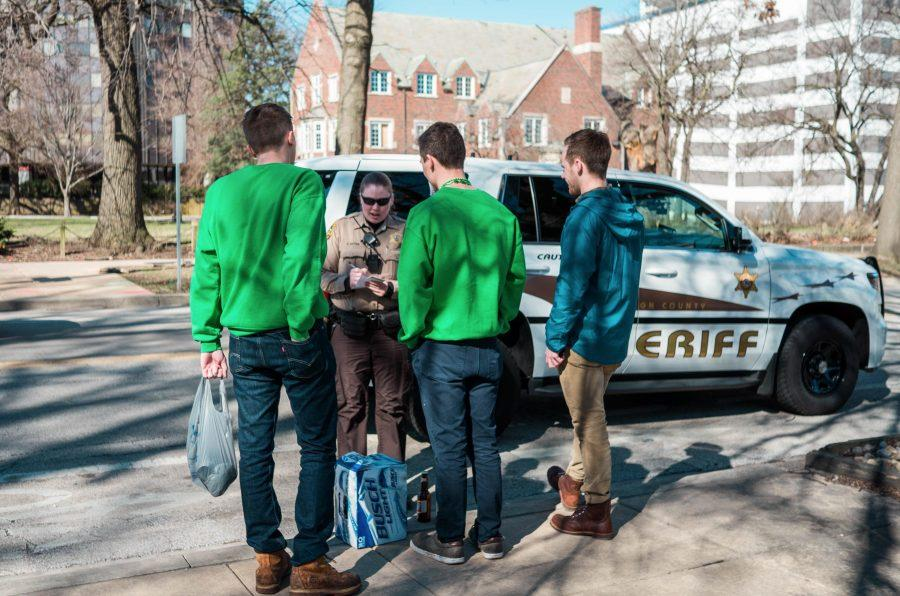 A police officer issuing tickets to three students around Fifth Street in the morning on Unofficial Day, March.3rd.