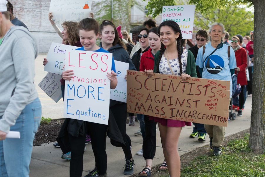 Champaign-Urbana community members march in downtown Champaign near the Orpheum Children's Museum as part of the March for Science. During Saturday's event, protestors campaigned for the U.S. Government to keep funding science programs and discouraged budget cuts.