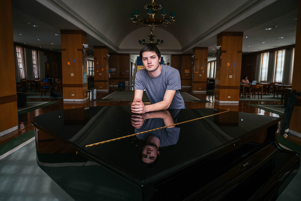 Tad Arndt, freshman in LAS, rests on the grand piano in Lincoln Avenue Residence Hall. Arndt writes his own music and uses his compositions as a force of social change.