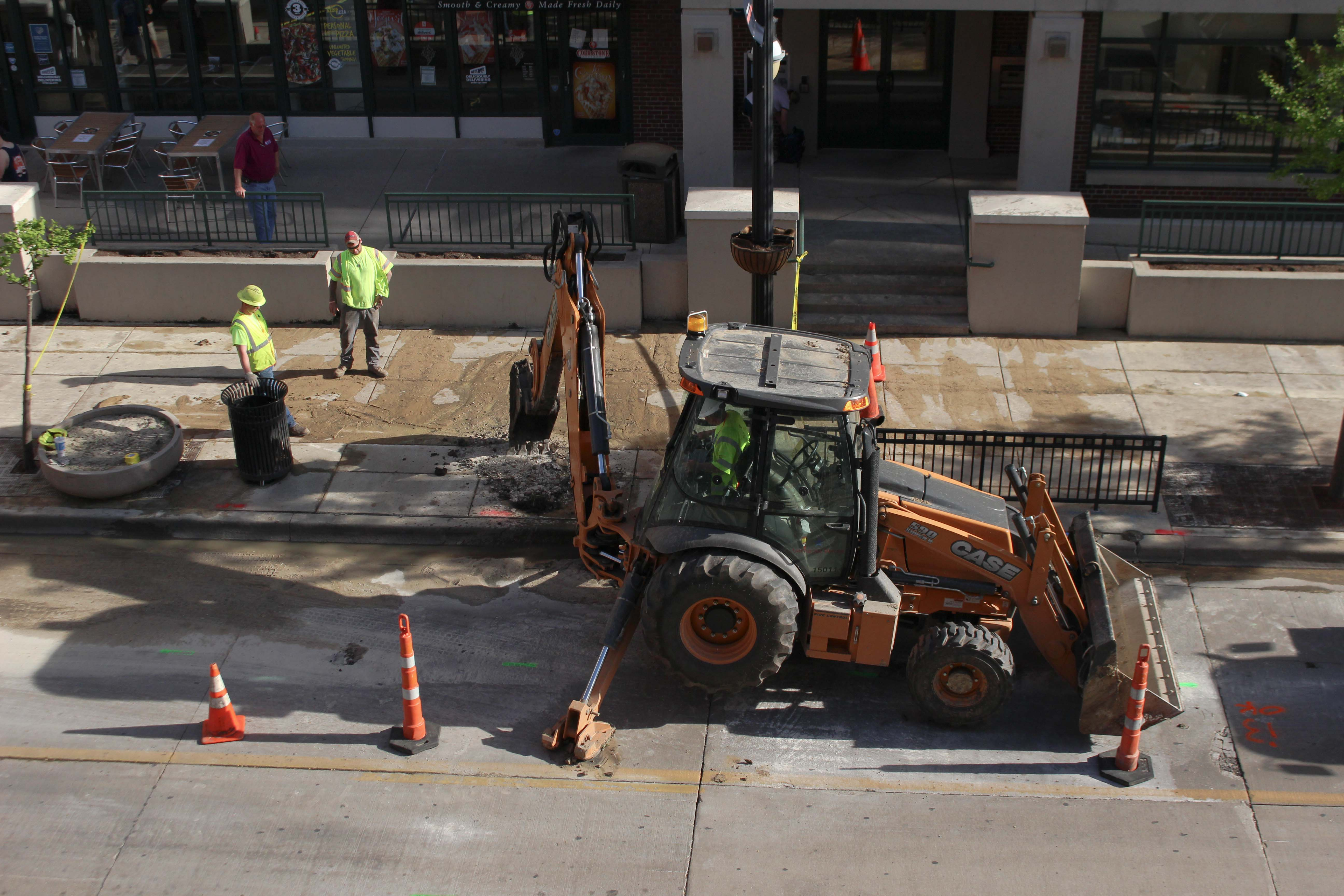 Construction workers fix a potential underground water line that broke  in front of Cold Stone Creamery on Green Street on Monday.