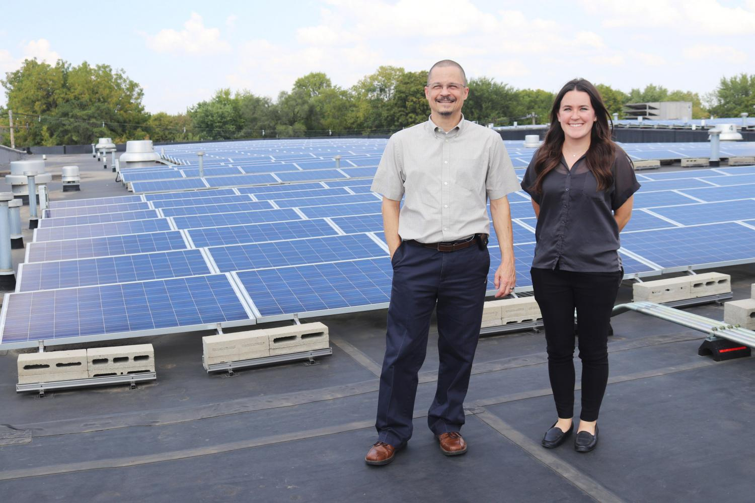 Managing Director, Karl Gnadt, and Grants Manager, Jane Sullivan, stand in front of their new solar panels that will help run the new CUMTD Hydrogen Fuel Cell Buses. The buses are set to be replaced some time in 2019.
