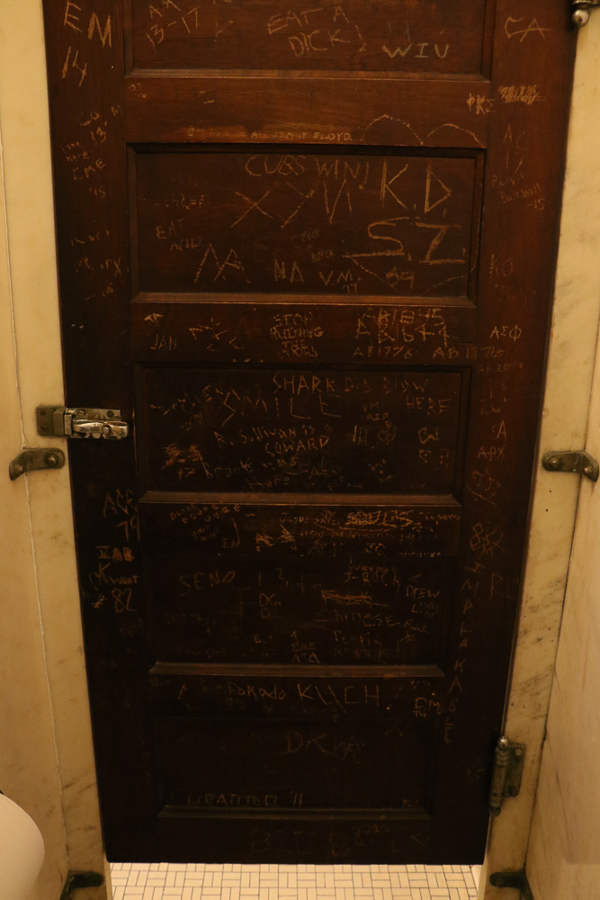 Graffiti on a bathroom stall in Altgeld Hall.