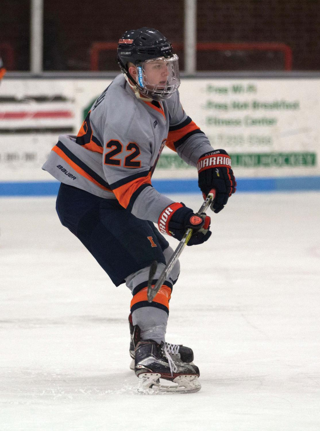 Tyler Opilka (22) passes the puck across the ice to a teammate at the Ice Arena on Saturday, Feb. 18. Illini fell to Robert Morris 3-2.
