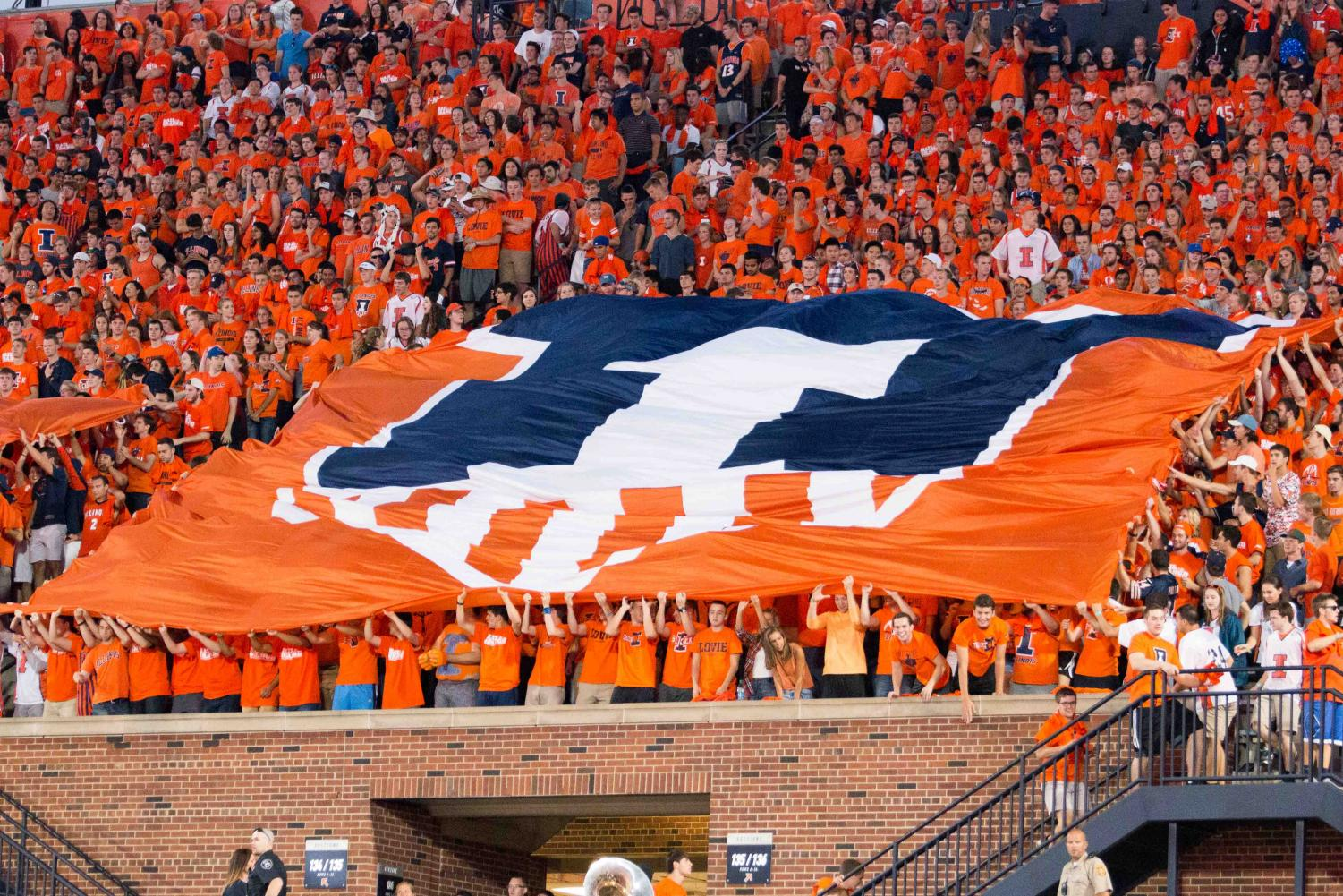 Students in Block I hold up the Illini shield flag during the game against North Carolina at Memorial Stadium on Sept. 10, 2016. Allie Hartlein, Block I communication chair, said students will perform an alumni-designed card stunt at the Homecoming football game on Saturday.