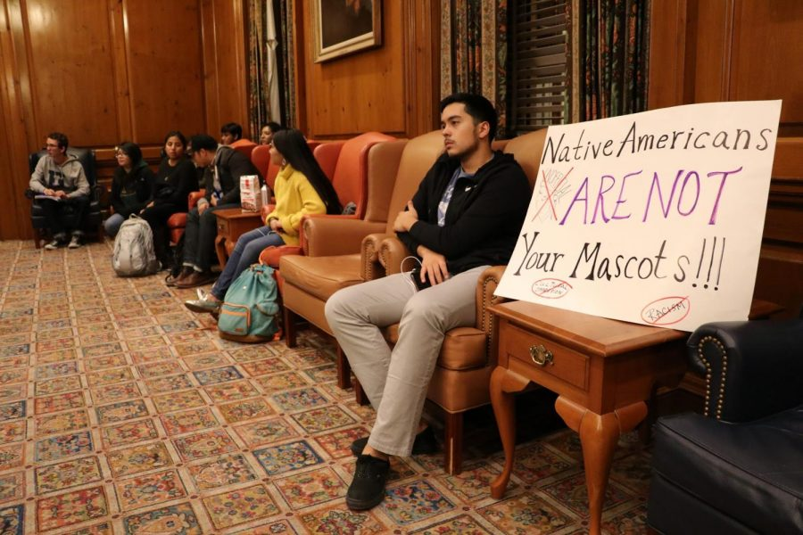 A student protester sits in on the Illinois Student Government meeting in the Illini Union Pine Room on Wednesday, Oct. 25, 2017. Chief Illiniwek made an appearance in the Homecoming Parade that year, so Illinois Student Government boycotted the parade in support of Native American students.