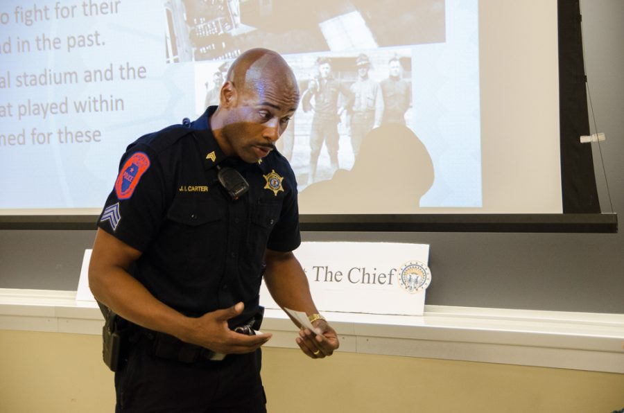 Police Sergeant James Carter of the UIPD talks with a woman who barged into the meeting and began destroying Chief Illiniwek posters. The woman was then removed from the meeting room by police.