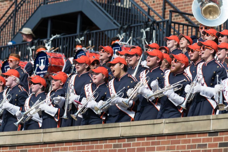 Members of the Marching Illini cheer during an Illinois football game.