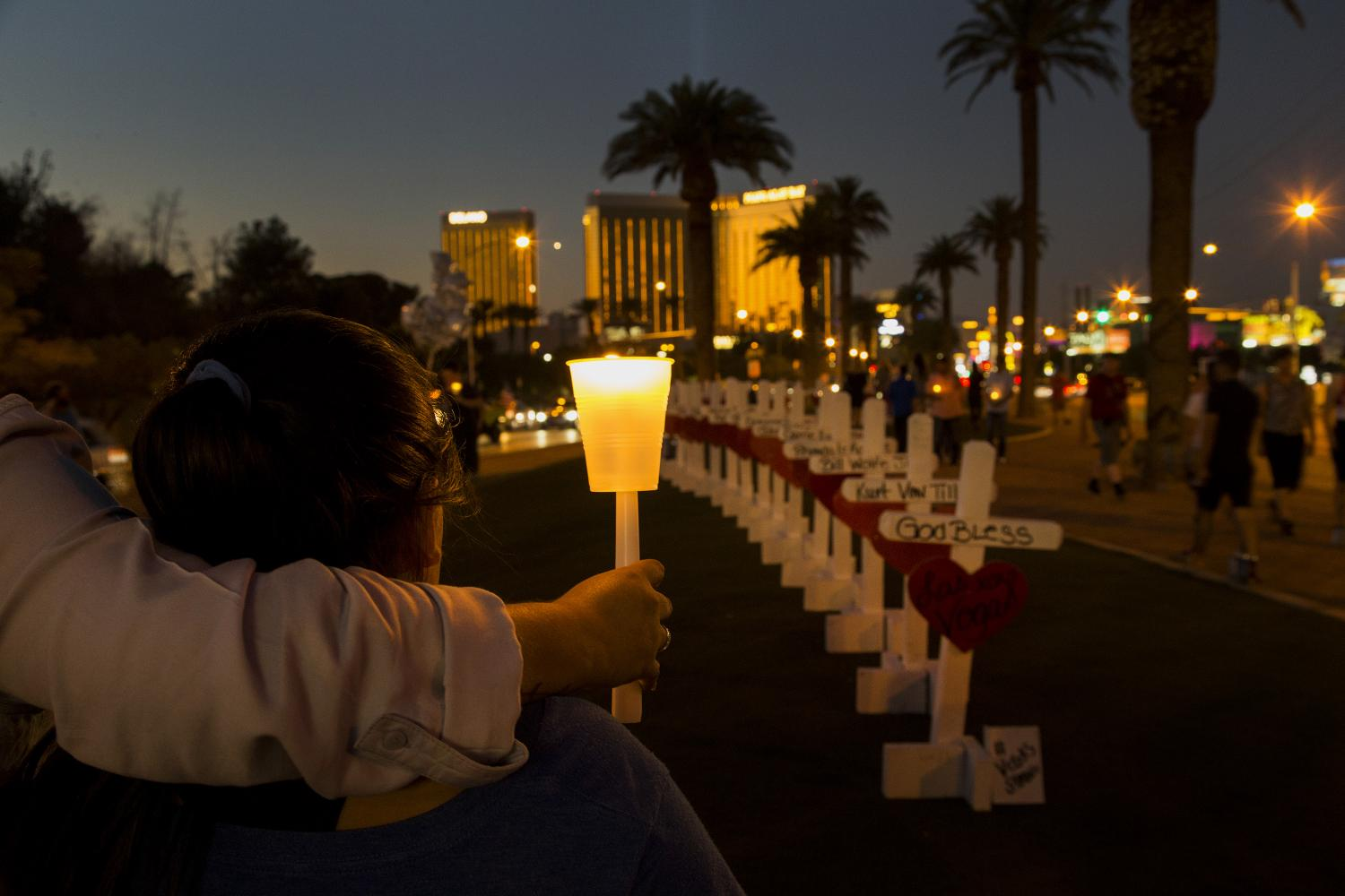 With wooden crosses bearing the names of those killed in the mass shooting, community members gather with candles to pay tribute to their loss on the median off Las Vegas Boulevard on October 5, 2017 in Las Vegas, Nevada. Mandalay Bay is in the background. Greg Zanis of Illinois drove all night to deliver the homemade crosses.