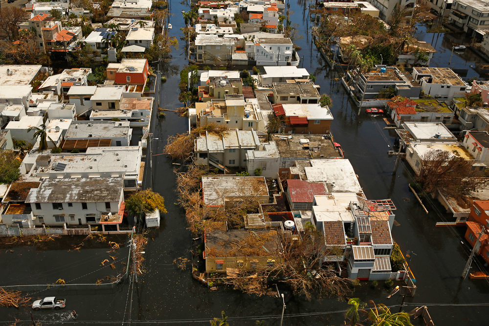 Nearly one week after hurricane Maria devastated the island of Puerto Rico, residents are still trying to get the basics of food, water, gas and money from banks. Much of the damage done was to electrical wires, fallen trees, and flattened vegetation, in addition to wooden home roofs torn off.