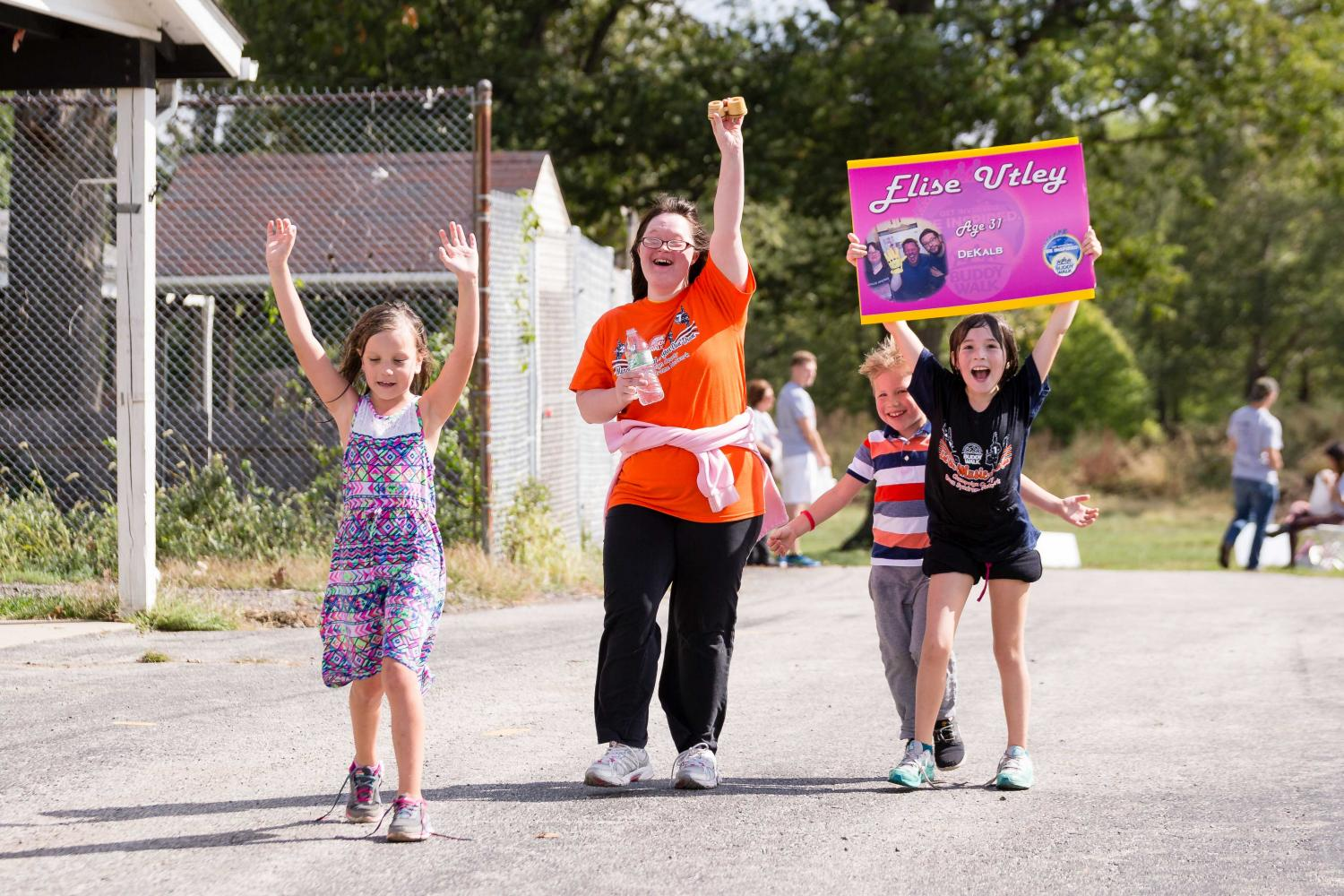 Elise Utley (orange) and her friends participate in the National Down Syndrome Society Buddy Walk at the Champaign County Fair Grounds on Saturday, October 7.