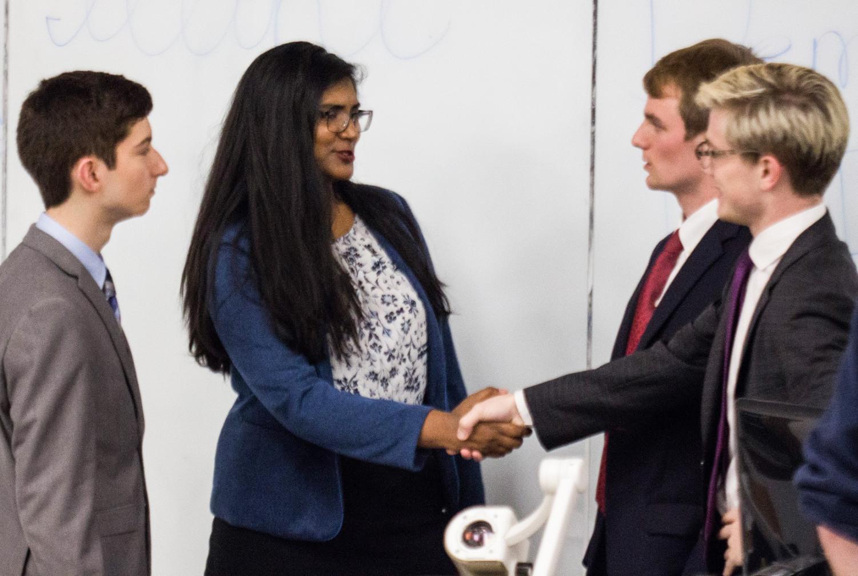Anusha Thotakura, a representative of the Illini Democrats, shakes Rick Hallman's hand, a representative of the Illini Republicans, at the Illini Democrats and Republicans debate on Nov. 2, 2017.