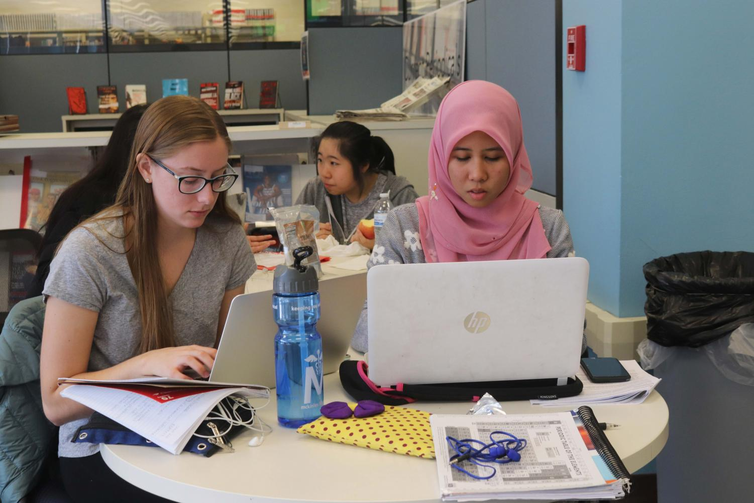 Sophomores Eva Bucke and Hazirah Muhamad work on a project together at the Undergraduate Library. Group projects can be beneficial because they allow students to learn how to work together.