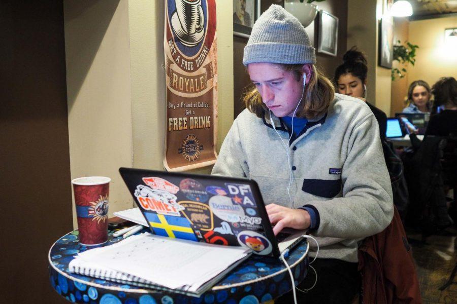 Isak Massman, senior in Business, studies in Espresso Royale with a beverage.