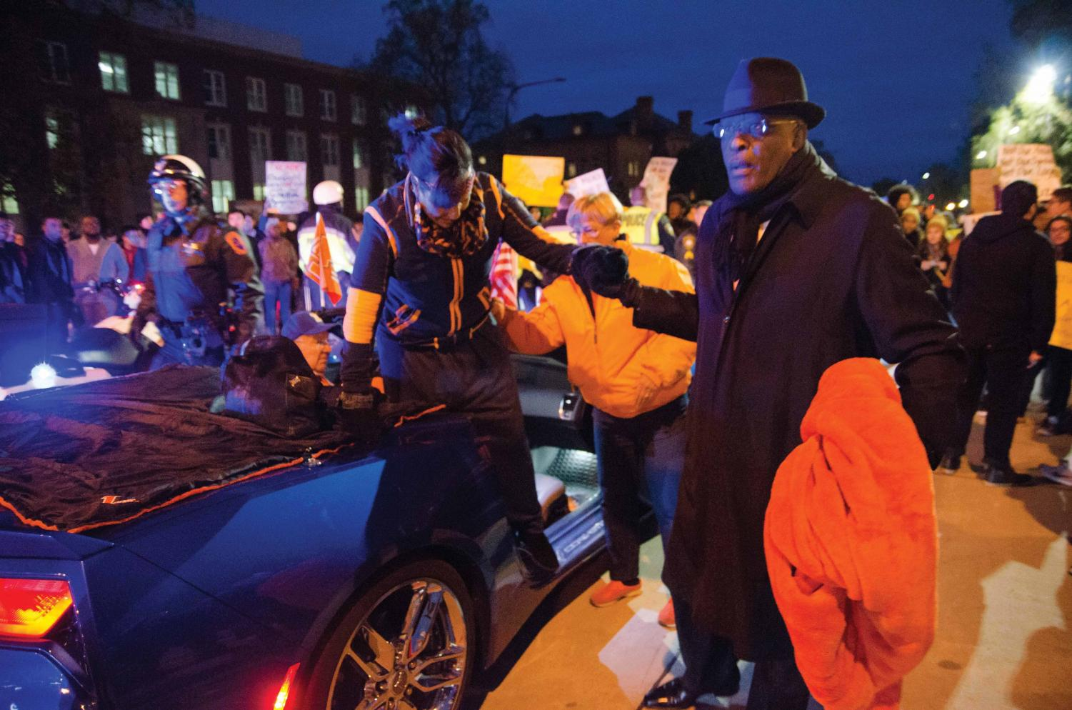 Chancellor Robert Jones helps Dr. Lynn Hassan Jones exit their car due to the 2017 Homecoming Parade being blocked by an anti-Chief Illiniwek protest on Friday. Earlier this week, following a meeting with alumni, students with indigenous backgrounds and Native American House staff, Illinois Student Government sent out information that it would be boycotting the parade.