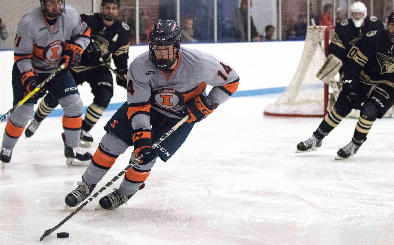 Neil Novosel (14) skates past Lindenwood's players to gain possession of the puck at the Ice Arena on Friday, Dec. 1.  Illini won in overtime 2-1.