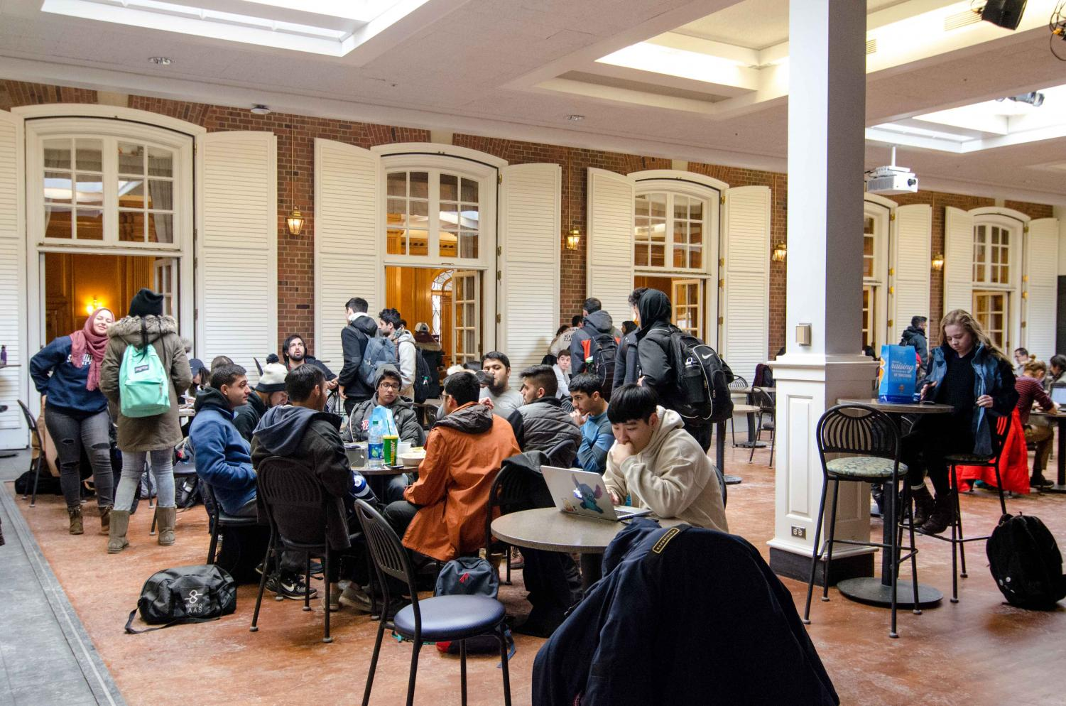 Students mingle on the first day of the Spring semester at the Illini Union Courtyard on Tuesday.