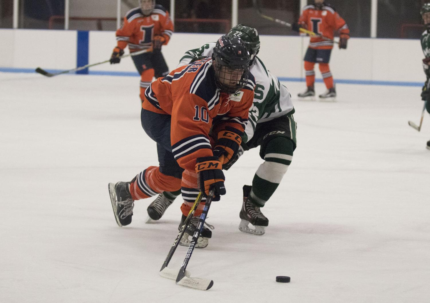 Drew Richter (10) fights off a Michigan State opponent to take the puck to the goal at the Ice Arena on Friday, Sept. 22, 2017. Illini beat MSU 4-1.