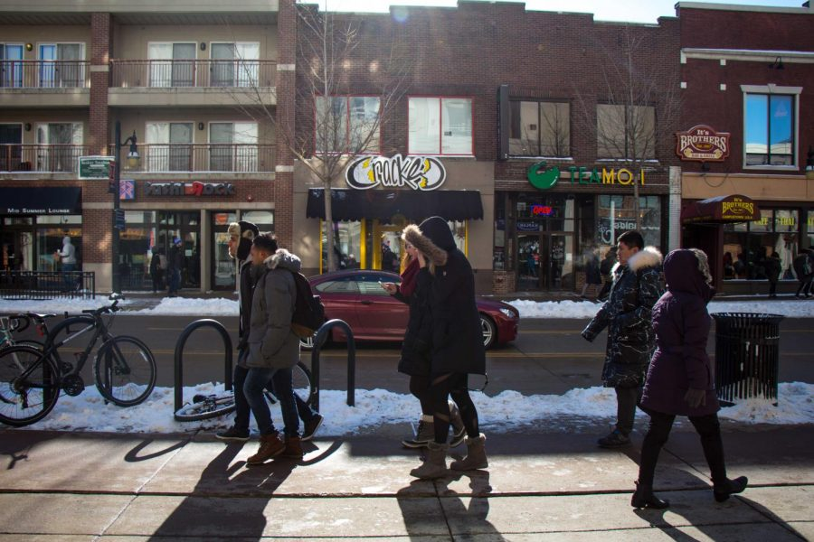 Students walk past an illegally parked car on Green Street on Jan. 17.